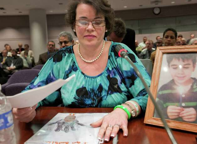 Veronique Pozner places her hand next to artwork made by her son Noah's  before testifying before a hearing of a legislative subcommittee reviewing gun laws at the Legislative Office Building in Hartford, Conn., Monday, Jan. 28, 2013.   Pozner, whose son Noah was killed in the Sandy Hook School shooting, told lawmakers about dropping off two of her daughters at the new Sandy Hook Elementary School in Monroe, and then visiting her son's grave, just five minutes away, to bring a teddy bear. (AP Photo/Jessica Hill) Photo: Jessica Hill, Associated Press / FR125654 AP