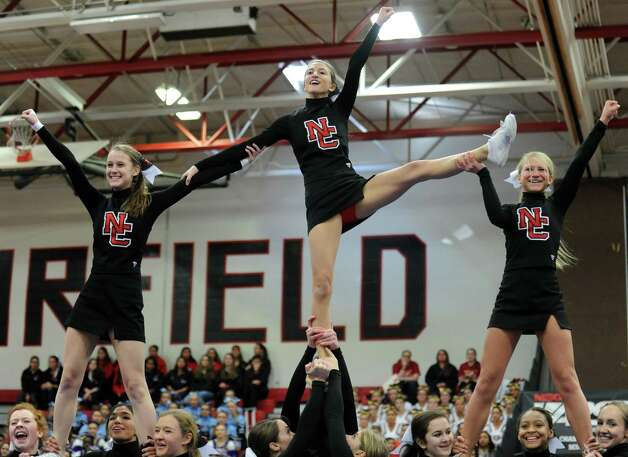 New Canaan's Bridget Callahan, Elana Kyriakos and Josephine Hardman, from left,  compete in the FCIAC cheerleading championships Saturday, Feb. 2, 2013 at Fairfield Warde High School in Fairfield, Conn. Photo: Autumn Driscoll / Connecticut Post