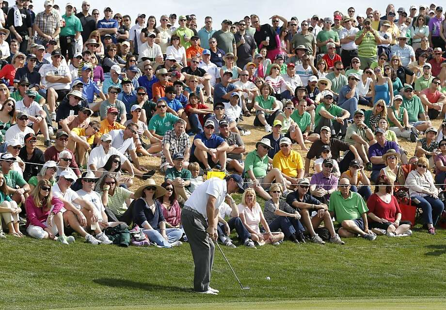Phil Mickelson, chipping on No. 6 in front of part of the biggest one-day crowd in golf history, is making an assault on tour and event records for low scores. Photo: Matt York, Associated Press