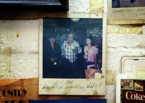 In a faded photo on the wall of Bill's BBQ in Ingram, TX, Walter Wesley Ellebracht Sr, center, poses with his son Walter Wesley Ellebracht Jr., left, and Jr's wife Joyce Ellebracht, right. Walter Wesley Ellebracht III, the son of Jr and Joyce, was killed in an automobile accident Jan. 20 on Highway 290 just out side Fredericksburg. He was just a young boy when his father and grandfather were arrested and their so-called Texas Slave Ranch was raided in 1984. Tuesday, Jan. 29, 2013 Photo: Bob Owen, San Antonio Express-News / © 2012 San Antonio Express-News