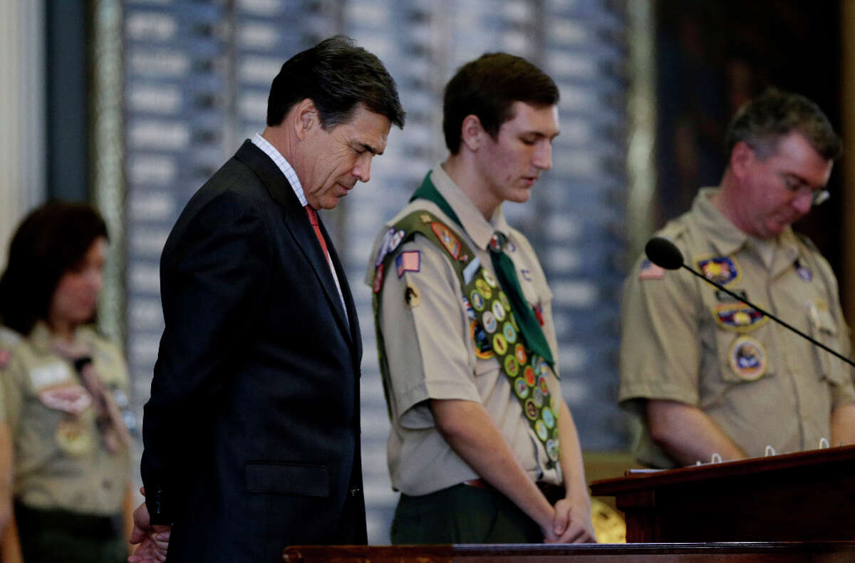 Gov. Rick Perry, left, bows his head for the invocation during the annual Boy Scouts Parade and Report to State in the House Chambers at the Texas State Capitol, Saturday, Feb. 2, 2013, in Austin, Texas. Perry says he hopes the Boy Scouts of America doesn't move soften its mandatory no-gays membership policy.