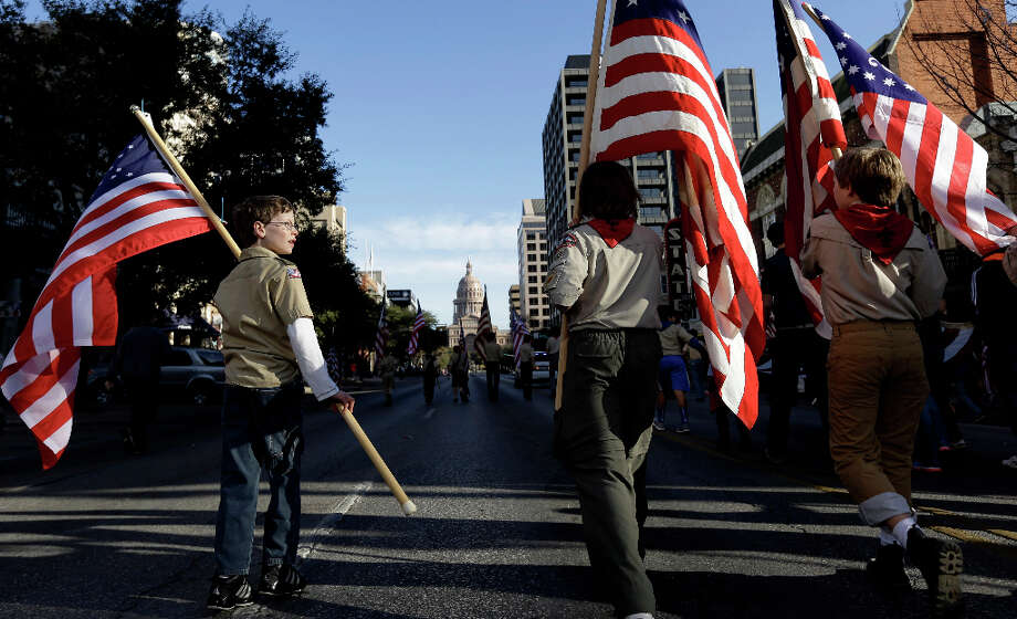 Boy Scouts carry U.S. flags up Congress Avenue towards the Texas Capitol during the annual Boy Scouts Parade and Report to State, Saturday, Feb. 2, 2013, in Austin, Texas. Gov. Rick Perry says he hopes the Boy Scouts of America doesn't move soften its mandatory no-gays membership policy. Photo: Eric Gay, Associated Press / AP