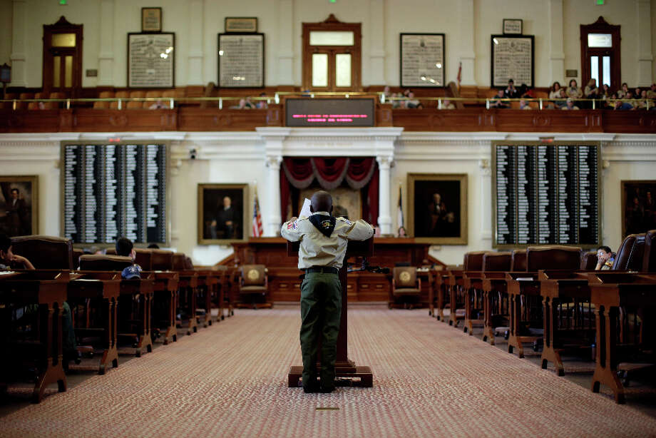 A Boy Scout reads a report from his home district to Gov. Rick Perry during the annual Boy Scouts Parade and Report to State in the House Chambers at the Texas State Capitol, Saturday, Feb. 2, 2013, in Austin, Texas. Perry says he hopes the Boy Scouts of America doesn't move soften its mandatory no-gays membership policy. Photo: Eric Gay, Associated Press / AP
