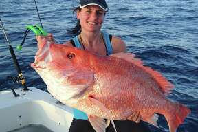 Tracy Allred holds a 38.25-inch red snapper she caught about 80 miles off Sabine Pass in January. The fish, which may have topped the Texas red snapper record of 38.13 pounds, was released because red snapper season is closed in Gulf water under federal control.