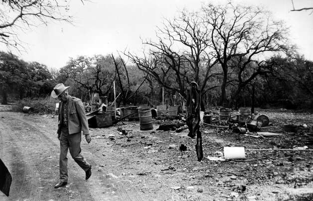 A Department of Public Safety trooper walks away from an area where a body reportedly was burned on the Ellebracht ranch. Photo: San Antonio Express-News