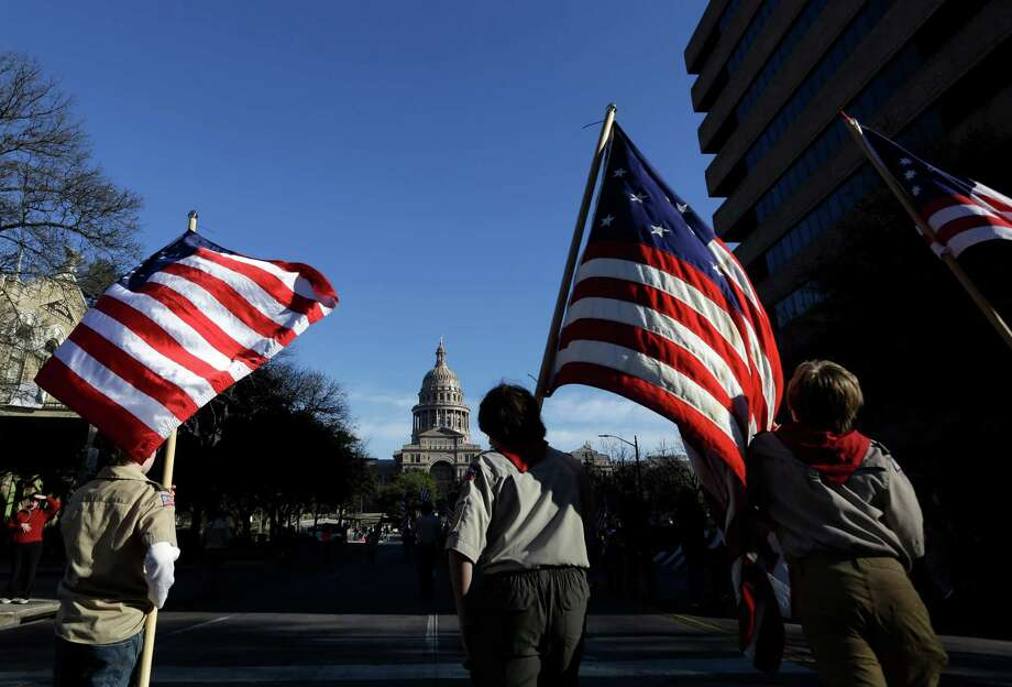 Boy Scouts carry U.S. flags up Congress Avenue towards the Texas Capitol during the annual Boy Scouts Parade and Report to State, Saturday, Feb. 2, 2013, in Austin, Texas.  (AP Photo/Eric Gay) Photo: Eric Gay, STF / AP