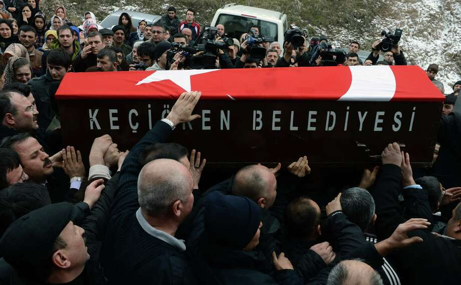 People carry the Turkish-flag-covered coffin of Mustafa Akarsu, a security guard killed when a suicide bomber attacked the U.S. Embassy in Ankara, Turkey, on Friday. Photo: Associated Press / AP