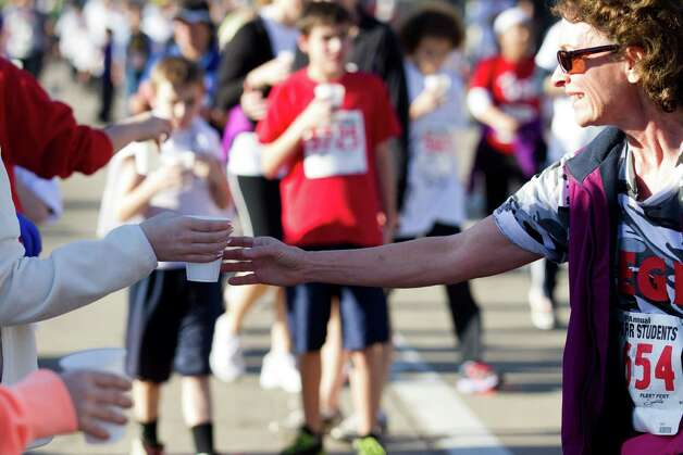 Runners grab water during the 8th Annual Steps for Students 5K Run/Walk Saturday, Feb. 2, 2013, in Houston. Photo: Brett Coomer, Houston Chronicle / © 2013 Houston Chronicle