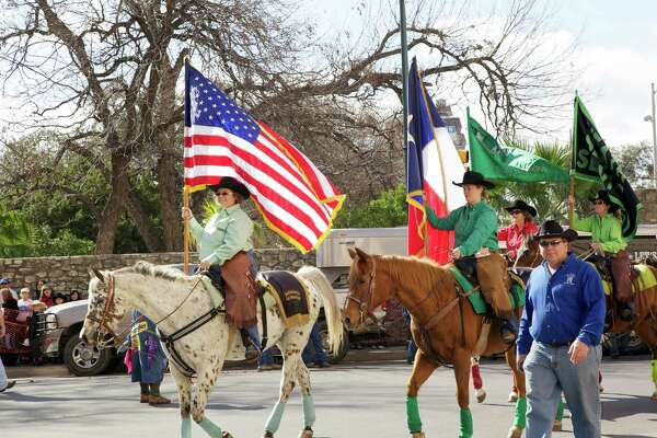 Spectators watch the Western Heritage Parade & Cattle Drive make its way through downtown San Antonio on Saturday, Feb. 2, 2013.