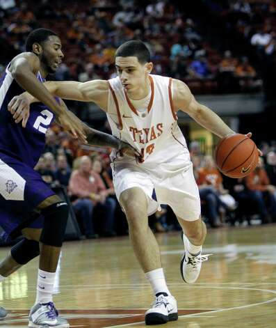 Texas forward Ioannis Papapetrou, right, drives around TCU forward Connell Crossland during the first half of an NCAA college basketball game, Saturday, Feb. 2, 2013, in Austin, Texas. (AP Photo/Michael Thomas) Photo: Michael Thomas, Associated Press / FR65778 AP