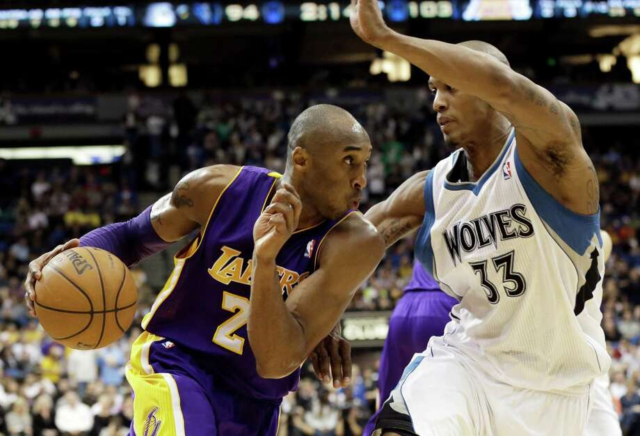 Los Angeles Lakers' Kobe Bryant, left, drives the basket on Minnesota Timberwolves' Dante Cunningham in the third quarter of an NBA basketball game Friday, Feb. 1, 2013 in Minneapolis.  Bryant scored 17 points and had 12 rebounds along with Pau Gasol as the Lakers won 111-100. (AP Photo/Jim Mone) Photo: Jim Mone
