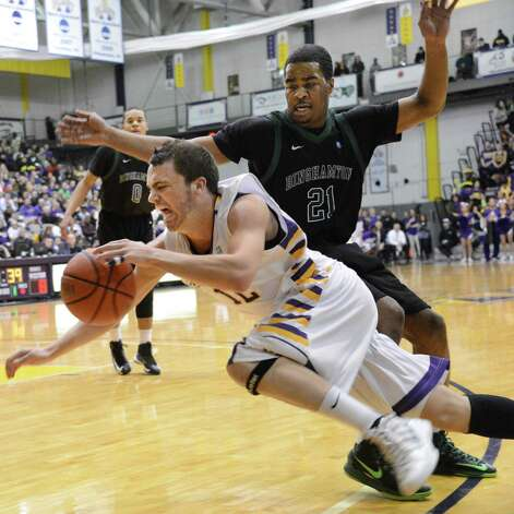 UAlbany's #12 Peter Hooley, left, drives inside Binghamton's #21Javon Ralling during Saturday's game at SEFCU arena in Albany  Feb. 2, 2013.  (John Carl D'Annibale / Times Union) Photo: John Carl D'Annibale / 00020948A