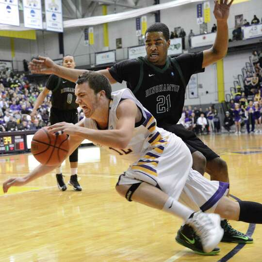 UAlbany's #12 Peter Hooley, left, drives inside Binghamton's #21Javon Ralling during Saturday's game