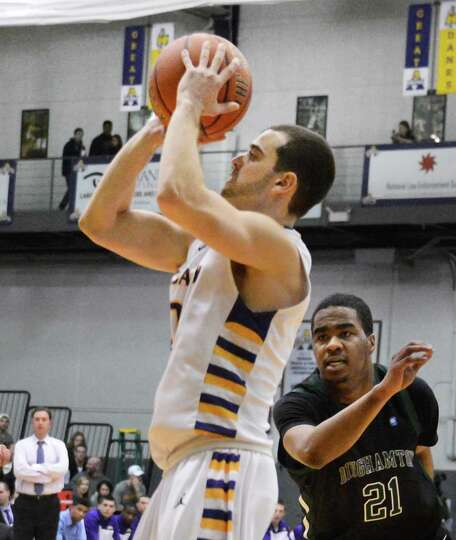 UAlbany's #0 Jacob Iati, left, gets around Binghamton's #21Javon Ralling for a three pointer during