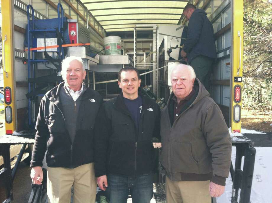 From left, Bob Phillips, president of Meals on Wheels of Greenwich, Scott Edwards, one of the owners of Surfside Bagels in Rockaway Beach, N.Y., and Peter Igoe, director and facilities committee chairman of Meals on Wheels of Greenwich, load up kitchen equipment that was donated by Meals on Wheels to the bagel shop, which was devastated by Hurricane Sandy. Photo: Contributed Photo