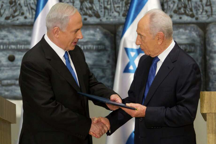Israeli Prime Minister Benjamin Netanyahu, left, receives a folder from Israeli President Simon Peres in a brief ceremony in the president's Jerusalem residence Saturday, Feb. 2, 2013.  Israel's president has asked Netanyahu to form the next government, and Netanyahu says he wants to advance peace talks with the Palestinians. (AP Photo/Jim Hollander, Pool) Photo: Jim Hollander