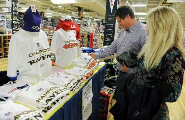 Co-workers Rob Howland of Saratoga Springs and Erica Gundrum of East Nassau look at a Superbowl display with Baltimore Ravens and San Francisco 49ers hats and t-shirts at the   Sports Zone store in Colonie Center on Wednesday Jan. 30, 2013 in Colonie, N.Y. Erica converted Rob into being a 49ers fan. (Lori Van Buren / Times Union) Photo: Lori Van Buren