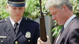 "FILE - In this April 25, 1994 file photo, President Bill Clinton holds a Colt AR-15 rifle during a ceremony in the Rose Garden of the White House in Washington, where he launched efforts to pass the assault weapons ban. Dayton, Ohio Police Lt. Randy Bean, whose fellow officer Steve Whalen was gunned down with an AR-15 in 1991, looks on at left. The White House has released a photo of President Barack Obama firing a gun, two days before he is set to travel to Minnesota to discuss gun control. It shows Obama shooting at clay targets on the range at Camp David, the presidential retreat in Maryland, where he says he engages in the sport ""all the time."" The image was released at a time when Obama is pushing a package of gun-control measures in response to the Newtown, Conn., school shooting. But the image of a U.S. president holding a gun is certainly nothing new. (AP Photo/Dennis Cook, File)"