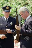 """FILE - In this April 25, 1994 file photo, President Bill Clinton holds a Colt AR-15 rifle during a ceremony in the Rose Garden of the White House in Washington, where he launched efforts to pass the assault weapons ban. Dayton, Ohio Police Lt. Randy Bean, whose fellow officer Steve Whalen was gunned down with an AR-15 in 1991, looks on at left. The White House has released a photo of President Barack Obama firing a gun, two days before he is set to travel to Minnesota to discuss gun control. It shows Obama shooting at clay targets on the range at Camp David, the presidential retreat in Maryland, where he says he engages in the sport """"all the time."""" The image was released at a time when Obama is pushing a package of gun-control measures in response to the Newtown, Conn., school shooting. But the image of a U.S. president holding a gun is certainly nothing new. (AP Photo/Dennis Cook, File)"""