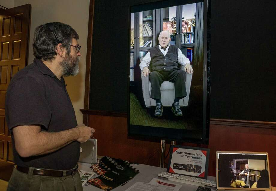 """In this photo taken Tuesday, Jan. 29, 2013, University of Southern California Institute for Creative Technologies, computer scientist David Traum, left, interacts with Holocaust survivor, Pinchas Gutter, seen on a """"Virtual Survivor Visualization,"""" at the USC campus in Los Angeles. A collaboration with the Shoah Foundation is digitizing aging Holocaust survivors to create three-dimensional holograms that would not only be able to tell their stories to future generations but to engage in dialogue with them. (AP Photo/Damian Dovarganes) Photo: Damian Dovarganes"""
