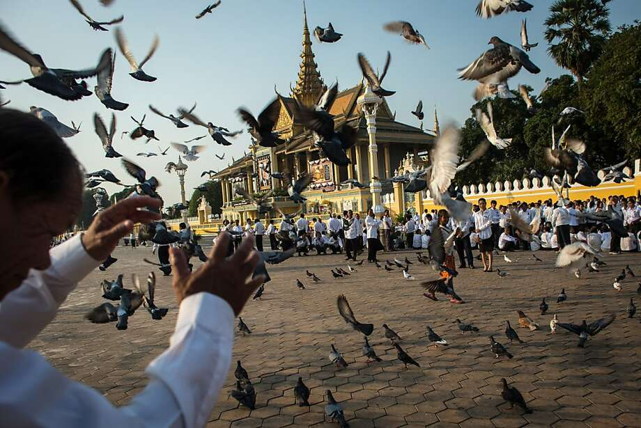 A man shields himself from flying pigeons as he waits with thousands of mourners outside the Royal Palace before being allowed to enter the cremation site to pay final respects to former King Norodom Sihanouk on February 2, 2013 in Phnom Penh, Cambodia. The former kings coffin was transported to the cremation site yesterday after being paraded through the capital in a lavish funeral procession. The cremation will take place on Monday the 4th of February, the funeral pyre will be lit by his wife and son King Norodom Sihamoni. Photo: Chris McGrath, Getty Images
