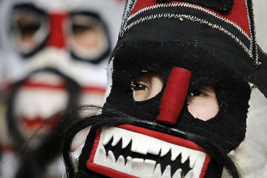 "A young  ""kukeri"" dancer carries her mask as she performs during  the 22nd edition of the International Festival of Masquerade Games ""Surva"" in the town of Pernik, Bulgaria Saturday, Feb. 2, 2013. Some 5000 participants take part in the festival devoted to an ancient Bulgarian pagan rite performed in the region. Photo: Valentina Petrova, Associated Press"