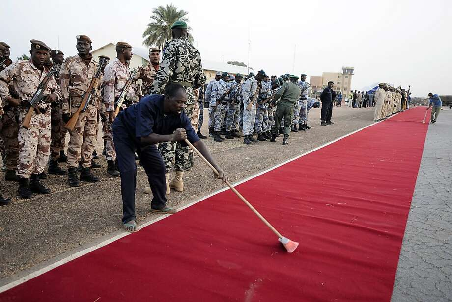 Last-minute security sweep:Unfortunately, Mali forget to vacuum the red carpet before rolling it out for the French and Malian heads of state at Mopti airport in Sevare. Photo: Pascal Guyot, AFP/Getty Images