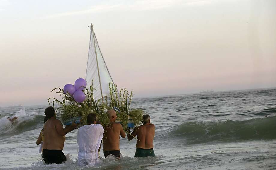 """Kindness is almost love,"" block party members and faithful carry a boat filled with flowers as an offering to the sea goddess Yemanja, during a pre-Carnival celebration in Rio de Janeiro, Brazil, Saturday, Feb. 2, 2013. Worshippers honor the deity, offering flowers and launching boats, large and small, into the ocean showing their gratitude for her blessings bestowed upon them. ( Photo: Silvia Izquierdo, Associated Press"