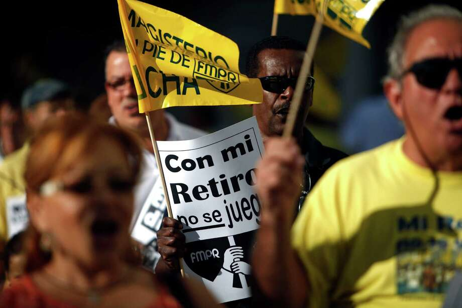 "A retiree carries a sign that reads, in Spanish, ""Do not play with my pension"" during a protest outside the government pension headquarters last week in San Juan, Puerto Rico. Photo: Ricardo Arduengo, STR / AP"