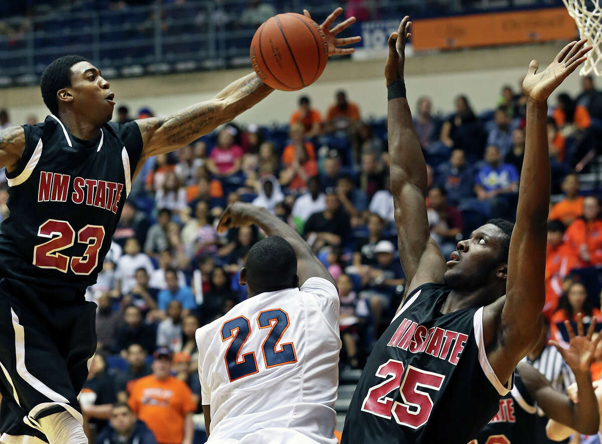 Aggie forward Renaldo Dixon (25) stays on his feet as teammate Daniel Mullings arrives to thwart the layup of UTSA guard Kannon Burrage in the first half as the Roadrunners host New Mexico State at the UTSA Convocation Center on February 2, 2013.