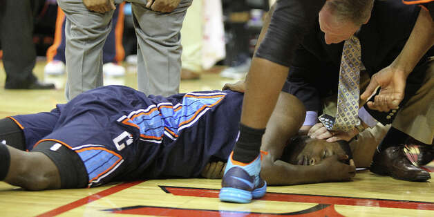 Charlotte Bobcats personnel help Michael Kidd-Gilchrist (14) who was responsive, and moved his limbs, but didn't open his eyes after an injury. Photo: Nick De La Torre, Chronicle / © 2010 Houston Chronicle