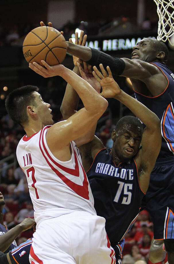Jeremy Lin (7) is met by Kemba Walker (15) and Bismack Biyombo (0) with great resistance on a drive to the basket. Photo: Nick De La Torre, Chronicle / © 2010 Houston Chronicle