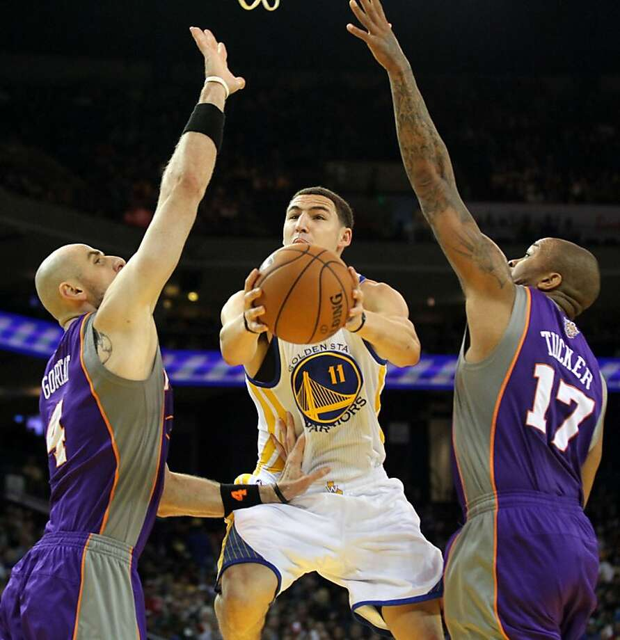 Golden State Warriors guard Klay Thompson (11) shoots between two Phoenix Suns defenders in the first half of their NBA basketball game Saturday, Feb. 2, 2013 at the Oakland Coliseum in Oakland California. Photo: Lance Iversen, The Chronicle