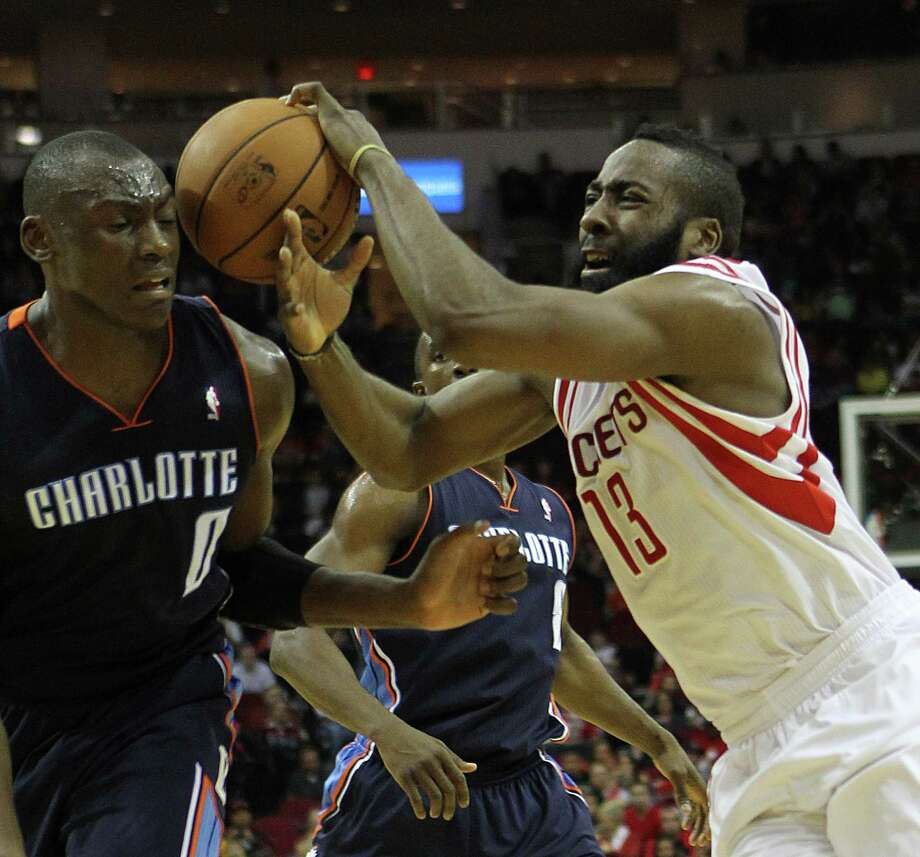 Charlotte's Bismack Biyombo (0) has the ball bounced off his head as the Rockets' James Harden (13) drives to the basket in the second quarter Saturday night. Photo: Nick De La Torre, Staff / © 2010 Houston Chronicle