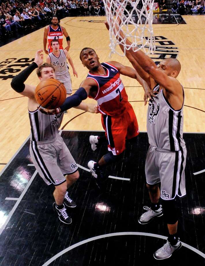 San Antonio Spurs' Tiago Splitter (left) and Tim Duncan defend Washington Wizards' John Wall during second half action Saturday Feb. 2, 2013 at the AT&T Center. The Spurs won 96-86. Photo: Edward A. Ornelas, San Antonio Express-News / © 2013 San Antonio Express-News