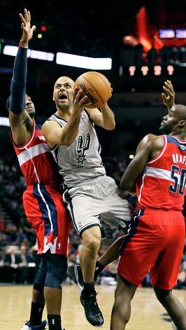 San Antonio Spurs' Tony Parker drives to the basket between Washington Wizards' John Wall (left) and Emeka Okafor during first half action Saturday Feb. 2, 2013 at the AT&T Center. Photo: Edward A. Ornelas, San Antonio Express-News / © 2013 San Antonio Express-News