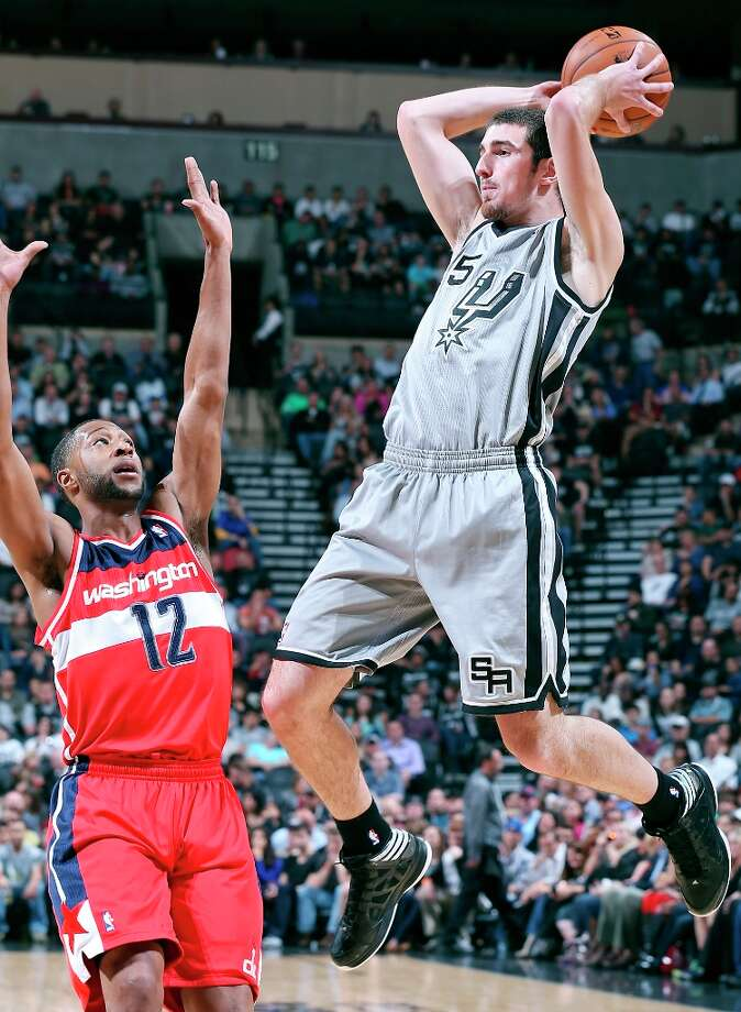San Antonio Spurs' Nando De Colo looks to pass over Washington Wizards' A.J. Price during first half action Saturday Feb. 2, 2013 at the AT&T Center. Photo: Edward A. Ornelas, San Antonio Express-News / © 2013 San Antonio Express-News