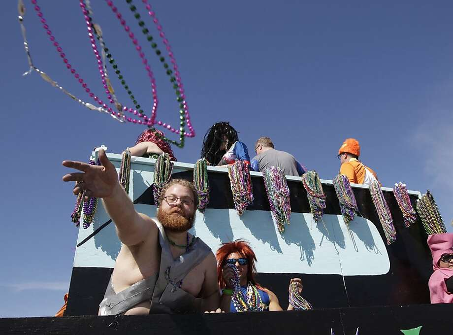 Float riders throw beads to the crowd during the Mystic Krewe of Aquarius 25th annual Mardi Gras Kick off Parade on the Seawall in Galveston, Texas on Saturday afternoon February 2, 2013.  Photo: Kevin M. Cox, Associated Press