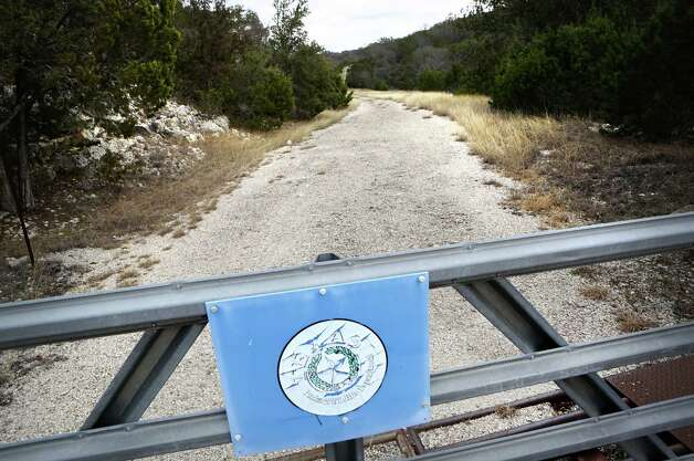 A weathered Texas Parks and Wildlife Department sign hangs on the locked gate, Tuesday, Jan. 29, 2013, that leads to what was the Ellebracht Ranch on Highway 27 in Mountain Home, TX. The state now owns the land that has a constant flowing spring which flows to the Heart of the Hills Fisheries Science Center just to the south.  Walter Wesley Ellebracht III, was killed in an automobile accident earlier this month on Highway 290 just out side Fredericksburg. He was just a young boy when his father and grandfather were arrested and their so-called Texas Slave Ranch was raided in 1984. Photo: Bob Owen, San Antonio Express-News / © 2012 San Antonio Express-News