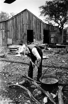 """Kerr County Sheriff Cliff Greeson inspects a pit where """"slaves"""" cooked their meals. In the background is the barn where the prisoners were chained to bunk beds at night. Photo: San Antonio Express-News"""
