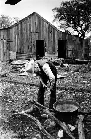 "Kerr County Sheriff Cliff Greeson inspects a pit where ""slaves"" cooked their meals. In the background is the barn where the prisoners were chained to bunk beds at night. Photo: San Antonio Express-News"