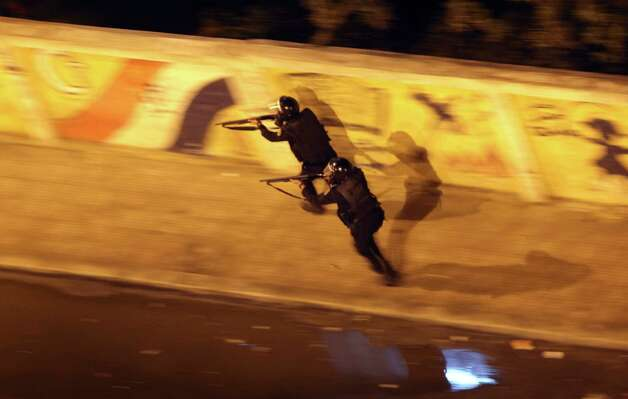 Egyptian riot police run with their weapons during clashes next to the presidential palace in Cairo, Egypt, Friday, Feb. 1, 2013. Protesters denouncing Egypt's Islamist president hurled stones and firebombs through the gates of his palace gates on Friday, clashing with security forces who fired tear gas and water cannons, as more than a week of political violence came to Mohammed Morsi's symbolic doorstep for the first time. Photo: AP