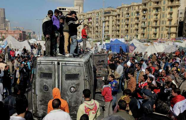 Egyptian protesters celebrate the capture of a state security armored vehicle that demonstrators commandeered during clashes with security forces and brought to Tahrir Square in Cairo, Egypt, Tuesday, Jan. 29, 2013. Egypt s army chief warned Tuesday of the 'the collapse of the state' if the political crisis roiling the nation for nearly a week continues, but said the armed forces will respect the right of Egyptians to protest. Photo: AP