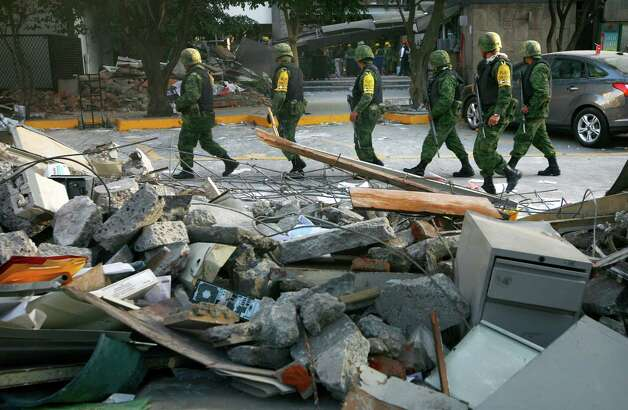 Soldiers patrol next to debris caused by an explosion at the state-owned oil company PEMEX office complex in Mexico City, Friday Feb. 1, 2013. Rescuers searched for survivors Friday and authorities promised a thorough investigation after an office building blast killed 32 people and injured 121 at the headquarters of Mexico's state-owned oil company, Petroleos Mexicanos. Photo: AP