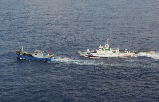 In this photo released by Japan Coast Guard 11th Regional Headquarters, a Japan Coast Guard patrol boat, right, approaches a Chinese fishing boat off the northeastern coast of Miyako island, about 200 kilometers (124 miles) southwest of the disputed islands, called Senkaku in Japan and Diaoyu in China, Saturday, Feb. 2, 2013. Coast Guard officials said they arrested the Chinese captain of the 100-ton boat earlier Saturday for suspected illegal fishing inside Japanese exclusive economic waters. (AP Photo/Japan Coast Guard 11th Regional Headquarters)  Photo: AP
