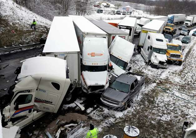 Police and emergency personal work the scene of a pileup involving more than 40-vehicles on Interstate 70 in Plainfield, Ind., Thursday, Jan. 31, 2013. The crash closed the interstate in both direction and authorities reported at least seven minor injuries. Photo: AP