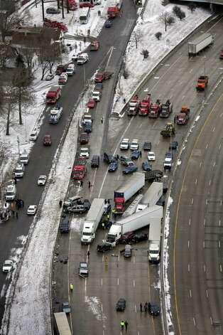 Emergency personnel respond at the scene of one of a mile-long series of crashes along Interstate 75 on the southwest side of Detroit Thursday, Jan. 31, 2013. At least three people are dead, including two children, and 20 more were injured in the pileups. (AP Photo/Detroit Free Press, Romain Blanquart) Photo: AP