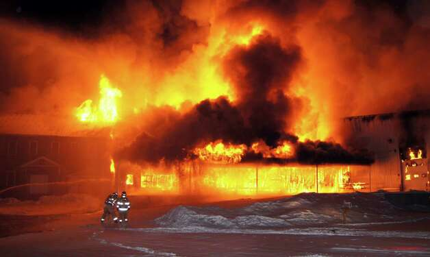 In this photo provided by Chuck Blaquiere, firefighters are dwarfed by a warehouse fully engulfed in flames behind a fireworks store in West Paris, Maine, Tuesday, Jan. 29, 2013.  Paris Fire Chief Brad Frost said firefighters from five communities responded and were warned to be careful of explosives in the building. Photo: AP