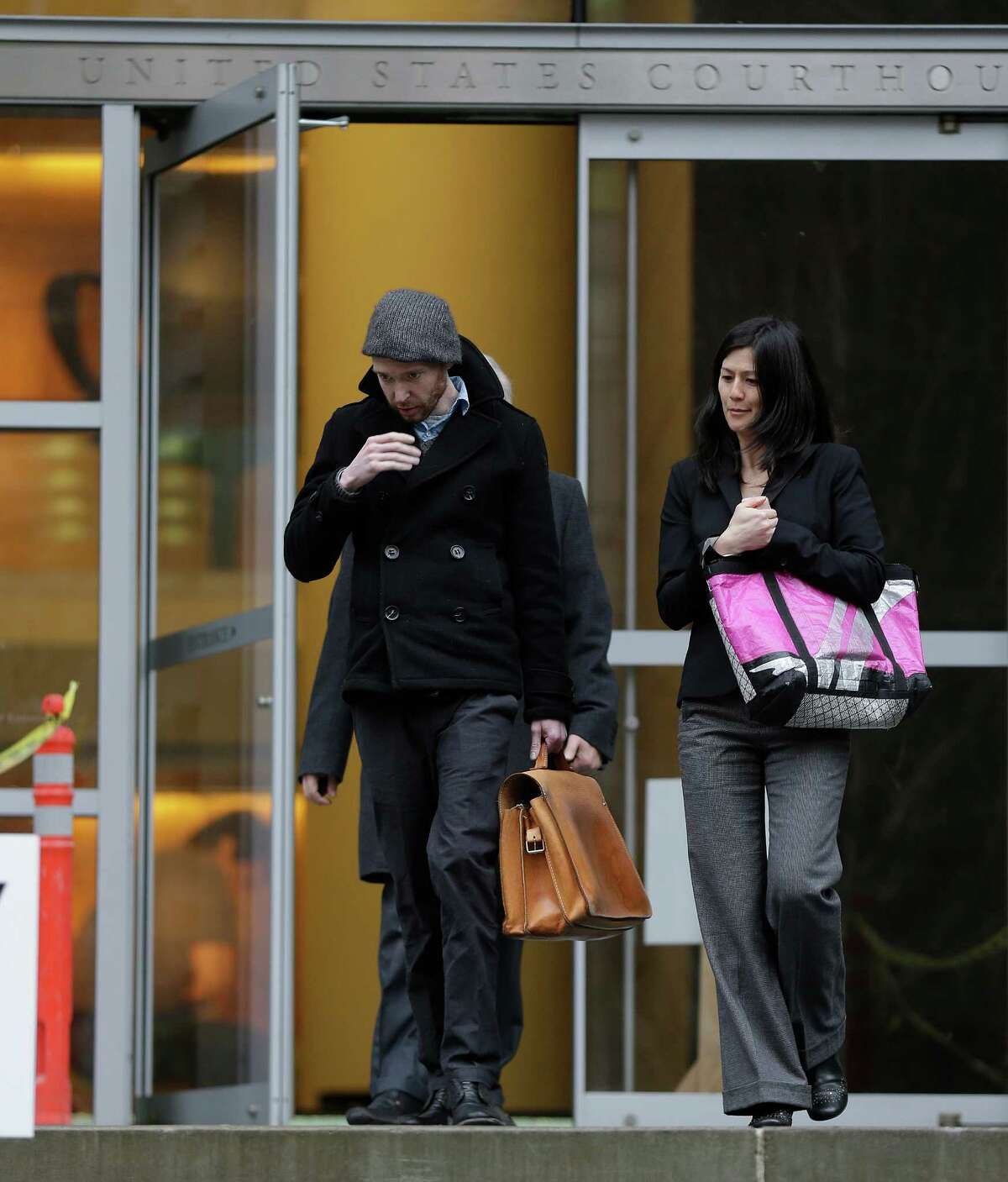 Musician Kasey Anderson, left, walks with his attorney, Corey Endo, Tuesday, Jan. 29, 2013, after Anderson made an initial appearance in U.S. District Court in Seattle. Anderson was arrested on charges he raised more than $525,000 for fictitious music projects - including one that purportedly involved Bruce Springsteen, Willie Nelson and Jack White.