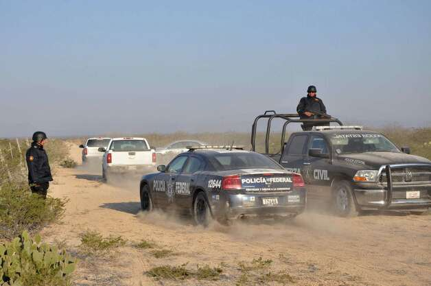 State and federal police drive along a dirt road leading to a ranch near the town of Mina, in northern Mexico, Monday, Jan. 28, 2013. At least eight bodies were found in a well near this ranch on Sunday near the site where 20 people went missing late last week, including members of a Colombian-style band, according to a state forensic official. Officials could not confirm whether the bodies belonged to 16 members of the band Kombo Kolombia and their crew, who were reported missing late last week after playing a private show in a bar in the neighboring town of Hidalgo, north of Monterrey. Photo: AP